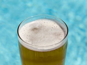 Glass of beer by pool